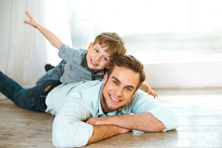 Nice family photo of little boy and his father. Boy and dad smiling and lying on wooden floor. Boy riding piggyback 免版税图像