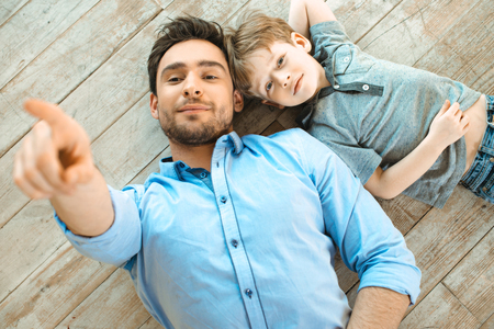 Nice family photo of little boy and his father. Boy and dad smiling and lying on wooden floor. Father pointing at camera