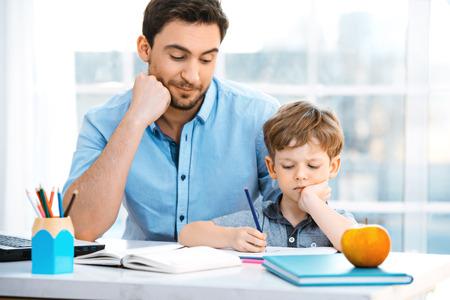 convivencia escolar: Bonita foto de familia del niño y su padre. Muchacho y papá sentado en la habitación con la ventana grande. Hombre joven que ayuda a su hijo a hacer la tarea Foto de archivo