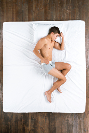 Top view photo of handsome Caucasian man. Young man sleeping on side on big white bed and wearing gray underwear