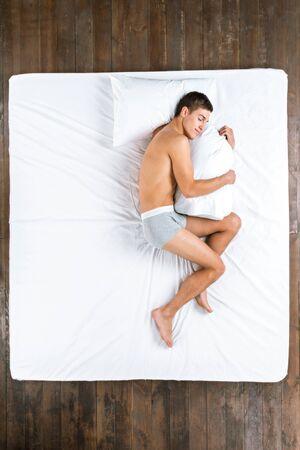 nackter junge: Draufsicht Foto der schönen kaukasischen Mann. Junger Mann auf der Seite auf großen weißen Bett schlafen, Kissen umarmt und graue Unterwäsche tragen