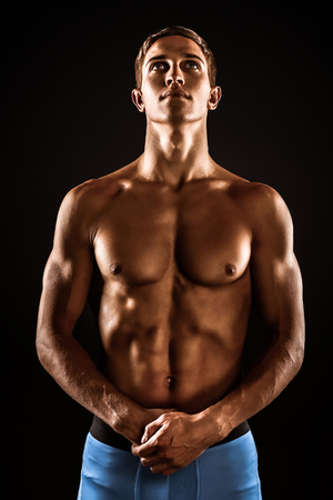 Young handsome well formed sporty man on black background. Fit sportsman looking up Imagens
