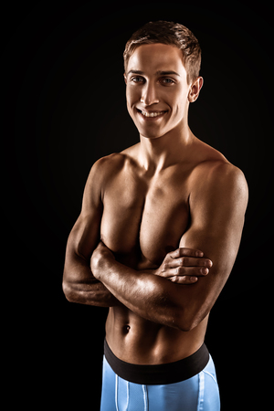Young handsome well formed sporty man on black background. Fit sportsman looking at camera and smiling