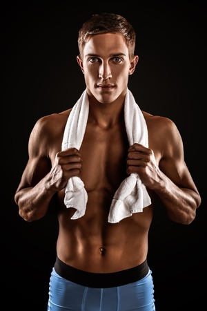 Young handsome well formed sporty man on black background. Fit sportsman with white towel on neck looking at camera