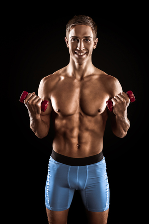 Young handsome well formed sporty man on black background. Fit sportsman exercising with red dumbbells and smiling Banco de Imagens - 107828092
