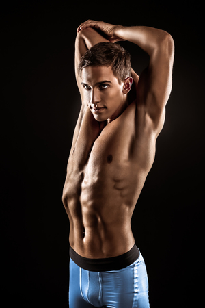 Young handsome well formed sporty man on black background. Fit sportsman stretching 版權商用圖片