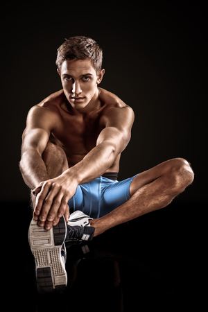 Young handsome well formed sporty man on black background. Fit sportsman stretching Imagens