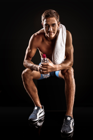 Young handsome well formed sporty man on black background. Fit sportsman resting. Man holding white towel and bottle of water