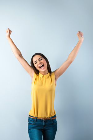 Photo of beautiful young business woman standing near gray background. Happy woman with yellow shirt and arms up cheerfully smiling Фото со стока