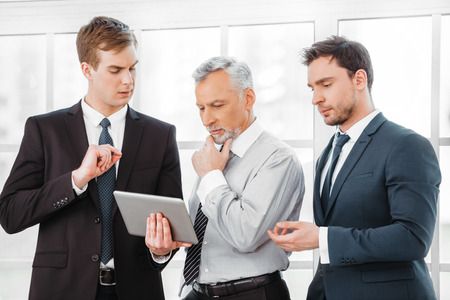 Photo of aged businessman and his colleagues. Businessmen working in office with big window. Men using tablet computer