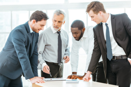 Photo d'un homme d'affaires âgé et de ses collègues lors d'une réunion. Hommes d'affaires travaillant au bureau avec grande fenêtre. Hommes discutant de graphiques Banque d'images