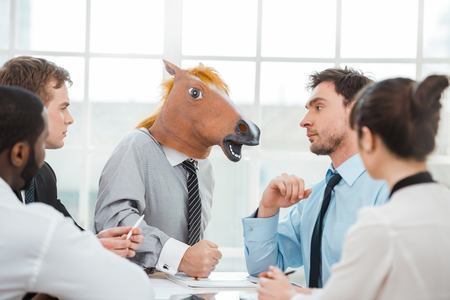 Funny photo of businessman wearing horse head and his colleagues. Businessmen and business woman working in office with big window