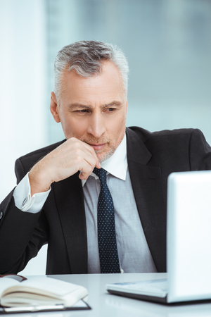 Portrait of aged businessman wearing suit and tie. Businessman in years is in office with big window. Boss using laptop