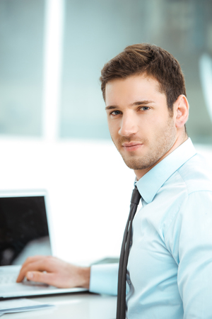 Portrait of young businessman in office with big window. Businessman using laptop and looking at camera Stok Fotoğraf