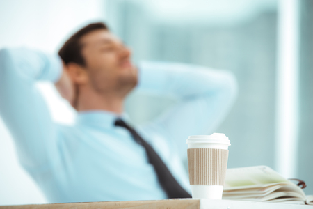 jornada de trabajo: Retrato de joven empresario en la oficina con ventana grande. Cansado de negocios de descanso, mientras que los días laborables. Centrarse en la taza de café