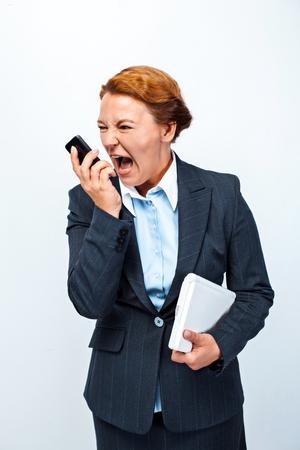 Foto de estudio de hermosa mujer de negocios pelirroja. Mujer de negocios gritando en el teléfono móvil y sosteniendo el portátil