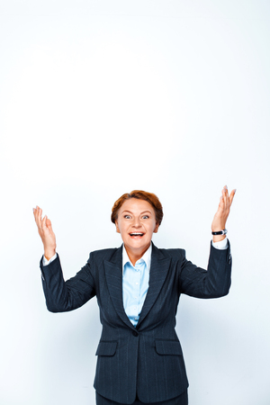 Studio shot of beautiful redheaded business woman. Business woman cheerfully looking at camera with hands up