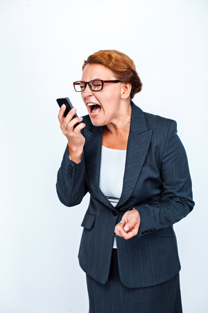 Studio shot of beautiful redheaded business woman. Business woman screaming at mobile phone