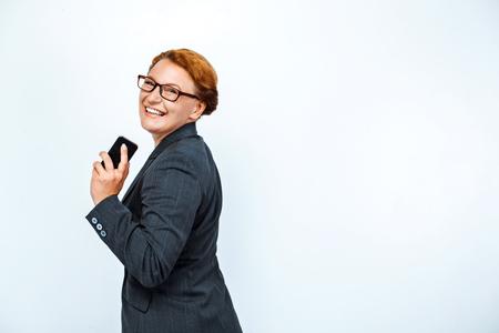 Foto de estudio de hermosa mujer de negocios pelirroja. Mujer de negocios sonriendo y sosteniendo teléfono móvil