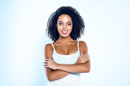 Bright picture of beautiful young mixed race woman with curly hair on white background. Girl with arms crossed looking at camera and smiling Stock Photo