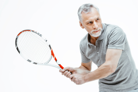 Horizontal photo of silver haired senior sportsman isolated on white background. Man playing tennis Stockfoto