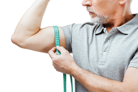Horizontal close up photo of silver haired senior sportsman isolated on white background. Man measuring biceps