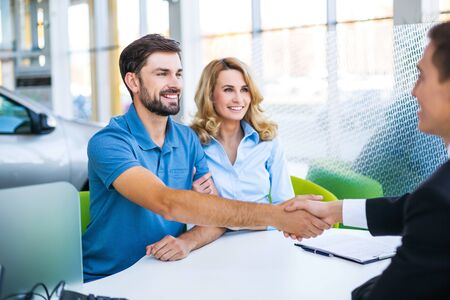 signing a contract: Photo of young male consultant and couple. Young woman and man buying new car in auto show. Signing of contract and shaking hands. Concept for car rental