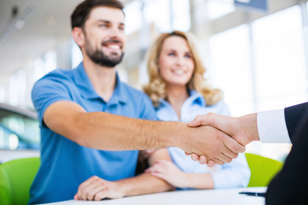 sell car: Photo of young male consultant and couple. Young woman and man buying new car in auto show. Signing of contract and shaking hands. Concept for car rental