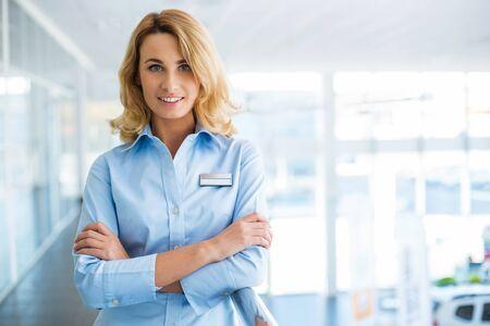 recepcionista: Retrato de joven empresaria. recepcionista joven que mira a la cámara y de pie en un bonito edificio moderno. entre la oficina