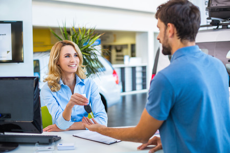 car showroom: Photo of young female consultant and buyer. Young man buying new car in car showroom. Buyer receiving keys