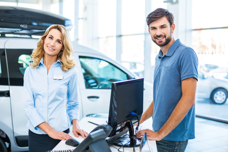 car showroom: Photo of young female consultant and buyer. Young man buying new car in car showroom
