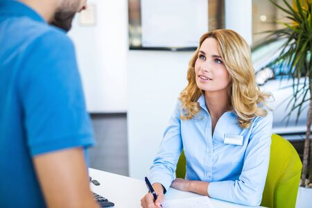 car showroom: Photo of young female consultant and buyer. Young man buying new car in car showroom. Signing of contract and insurance Stock Photo