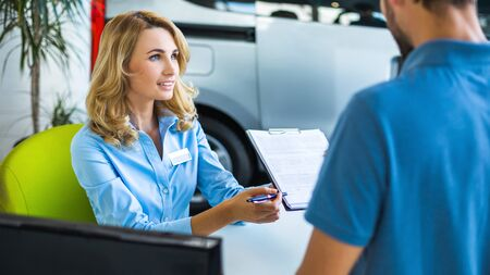 sell: Photo of young female consultant and buyer. Young man buying new car in car showroom. Signing of contract and insurance Stock Photo