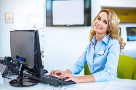 car showroom: Photo of young beautiful business woman in car showroom. Young business woman working with computer and looking at camera. Modern office interior