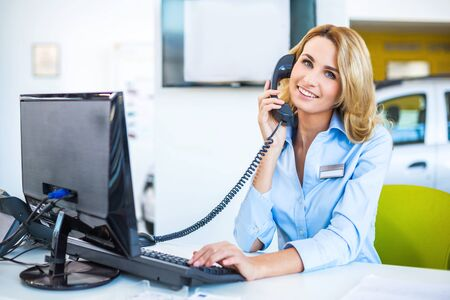 car showroom: Photo of young beautiful business woman in car showroom. Young business woman working with computer and talking on phone. Modern office interior Stock Photo