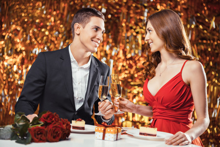 Romantic photo of beautiful couple on glitter gold background. Couple having date at Valentines Day. Lovers having dinner. There are glasses with champagne, desserts, roses and gift on table