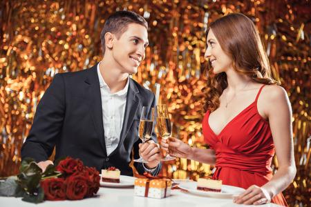 Romantische foto van mooie paar op goud achtergrond. Paar dat de datum op Valentijnsdag. Minnaars die diner. Er zijn glazen champagne, desserts, rozen en gift op tafel Stockfoto