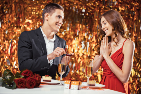 Romantic photo of beautiful couple on glitter gold background. Couple having dinner. There are glasses with champagne, desserts and roses on table. Man proposing to marry him with engagement ring