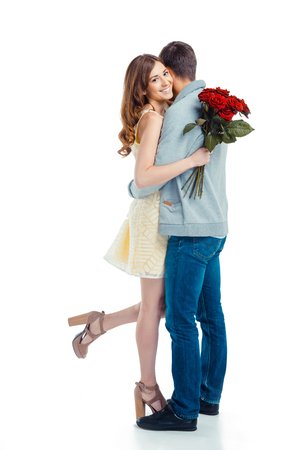 caucasian white: Romantic photo of beautiful couple on white background. Beautiful young woman hugging her boyfriend and holding nice bouquet of red roses