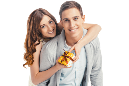 romantic hug: Romantic photo of beautiful couple on white background. Handsome young man and beautiful woman hugging. Woman holding gift from her boyfriend