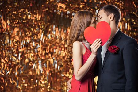반짝이 골드 배경에 아름 다운 부부의 낭만주의 사진. 잘 생긴 젊은 남자와 심장의 모양에 발렌타인 카드 뒤에 키스하는 아름 다운 여자