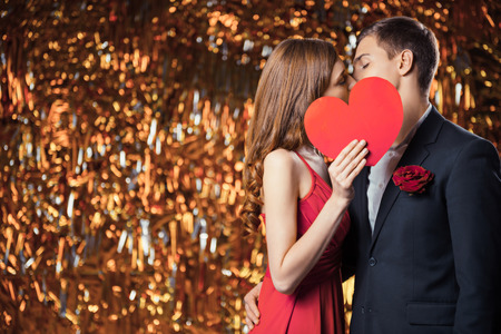 Romantic photo of beautiful couple on glitter gold background. Handsome young man and beautiful woman kissing behind Valentine card in shape of heart