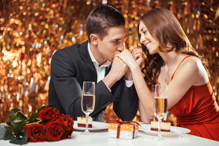 Romantic photo of beautiful couple on glitter gold background. Couple having date at Valentine's Day. Lovers having dinner. There are glasses with champagne, desserts, roses and gift on table