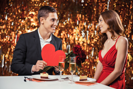 Romantic photo of beautiful couple on glitter gold background. Couple having date at Valentines Day. Lovers having dinner with champagne. Young man giving Valentine card and roses to his girlfriend