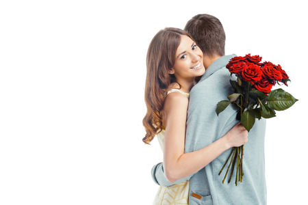parejas romanticas: Foto romántica de la bella pareja en el fondo blanco. Joven y bella mujer abrazando a su novio y la celebración de bonito ramo de rosas rojas