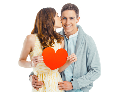 romantic background: Romantic photo of beautiful couple on white background. Handsome young man smiling and looking at camera while his girlfriend holding Valentine card and kissing him