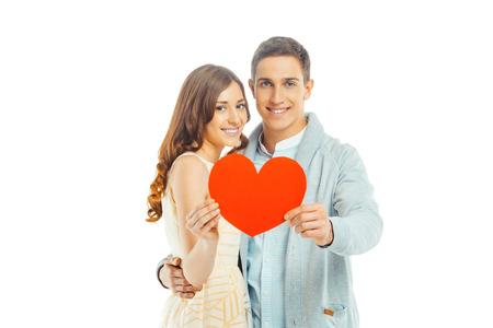 Foto romántica de la bella pareja en el fondo blanco. Apuesto joven y bella mujer sonriente, mirando la cámara y la celebración de tarjeta de San Valentín en forma de corazón Foto de archivo