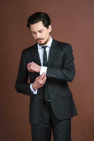 young  cuffs: Portrait of stylish handsome young man with mustache. Man wearing suit, correcting cuffs and standing against brown background Stock Photo