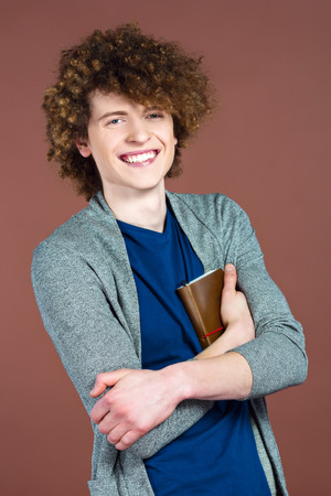 redheaded: Portrait of stylish handsome young redheaded man. Man standing against brown background, holding book and smiling