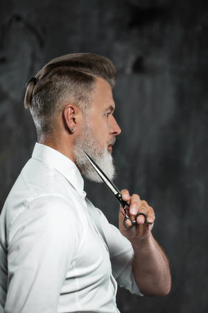 hair studio: Portrait of stylish professional hairdresser with beard. Man wearing shirt and holding scissors near his beard Stock Photo